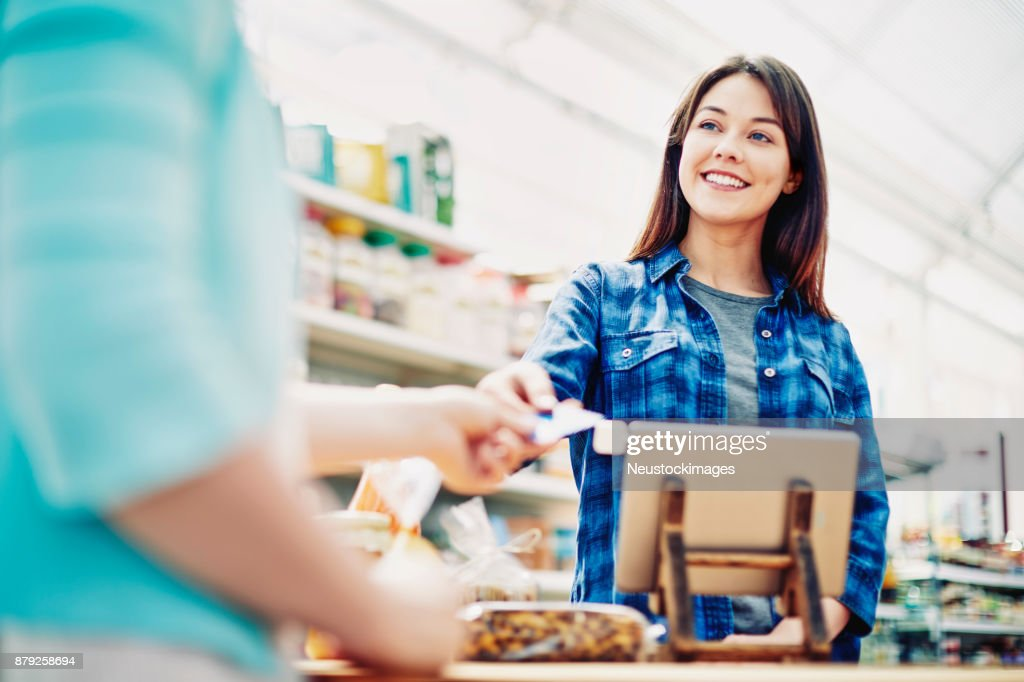 Smiling deli owner receiving credit card from customer in store : Stock Photo