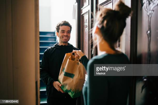 smiling delivery man delivering bag to woman standing at doorway - food photos et images de collection