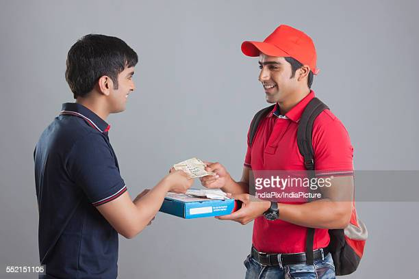 Smiling delivery man delivering pizza to customer against gray background