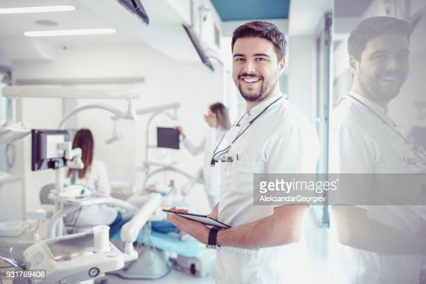 Smiling Dentist With Magnifier Glasses and Digital Tablet in Dental Clinic