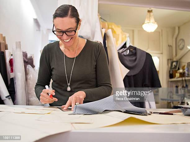 Smiling designer draws up garment panel