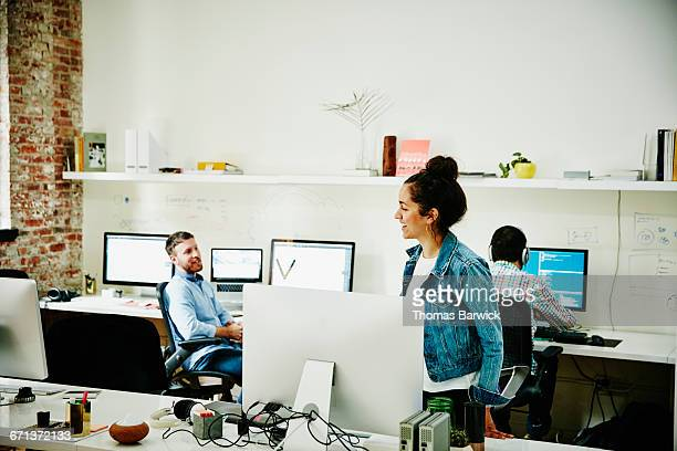Smiling designer in discussion with coworkers