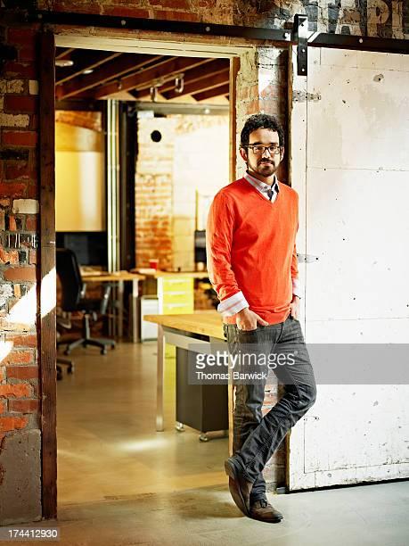 Smiling designer leaning on door frame in office