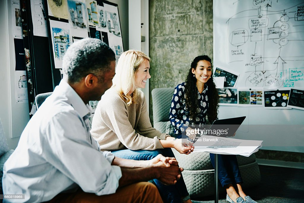 Smiling designers in project meeting in office : Stock Photo