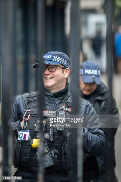 smiling diplomatic policeman behind the protective gates at downing st, westminster, london. - ambassador stock pictures, royalty-free photos & images