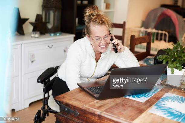 smiling disabled woman talking on mobile phone while looking at laptop in house - home icon stock photos and pictures