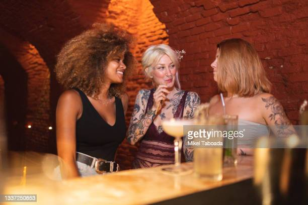 smiling diverse girlfriends with tattoos talking at bar counter - friendly match stock pictures, royalty-free photos & images