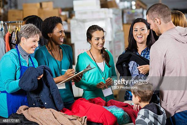 smiling diverse volunteers at charity clothing drive - clothing stock pictures, royalty-free photos & images