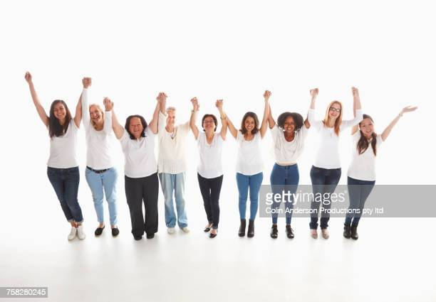 Smiling diverse women standing in a row with arms raised