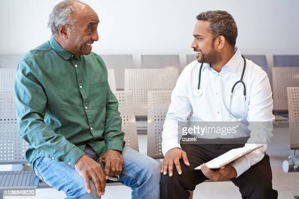 smiling doctor giving good news to senior man - african american man helping elderly stock pictures, royalty-free photos & images