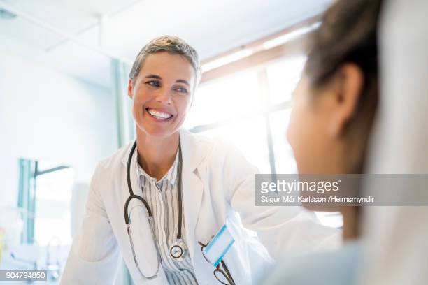 Smiling doctor looking at female patient in ward
