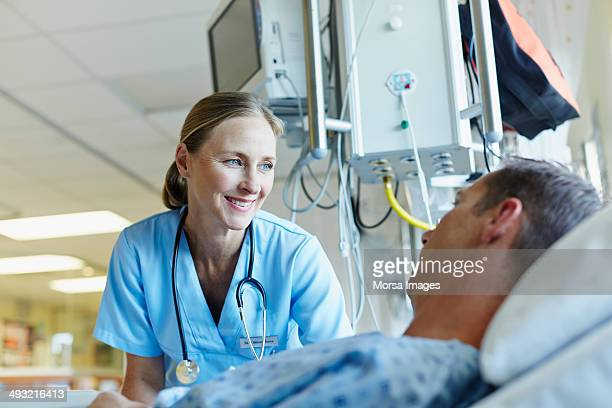 smiling doctor looking at patient in hospital ward - care stock pictures, royalty-free photos & images