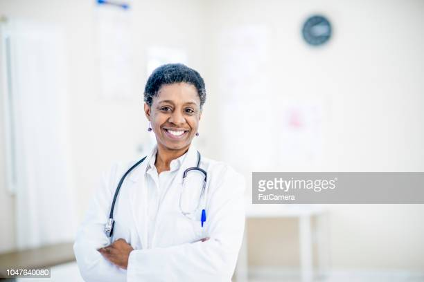 smiling doctor - black coat stock pictures, royalty-free photos & images