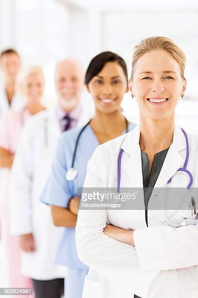 sorrir doutor em pé braços cruzados na frente da equipa médica - vertical imagens e fotografias de stock