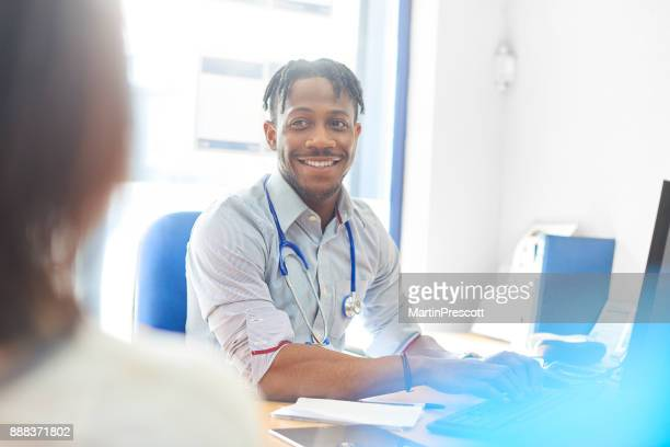 smiling doctor typing out prescription for patient on computer - good news stock pictures, royalty-free photos & images