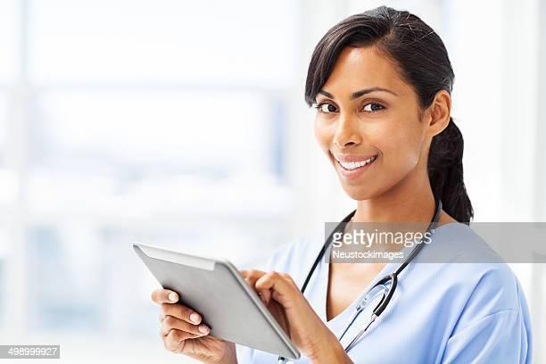 Souriant médecin à l'aide de tablette numérique à l'hôpital