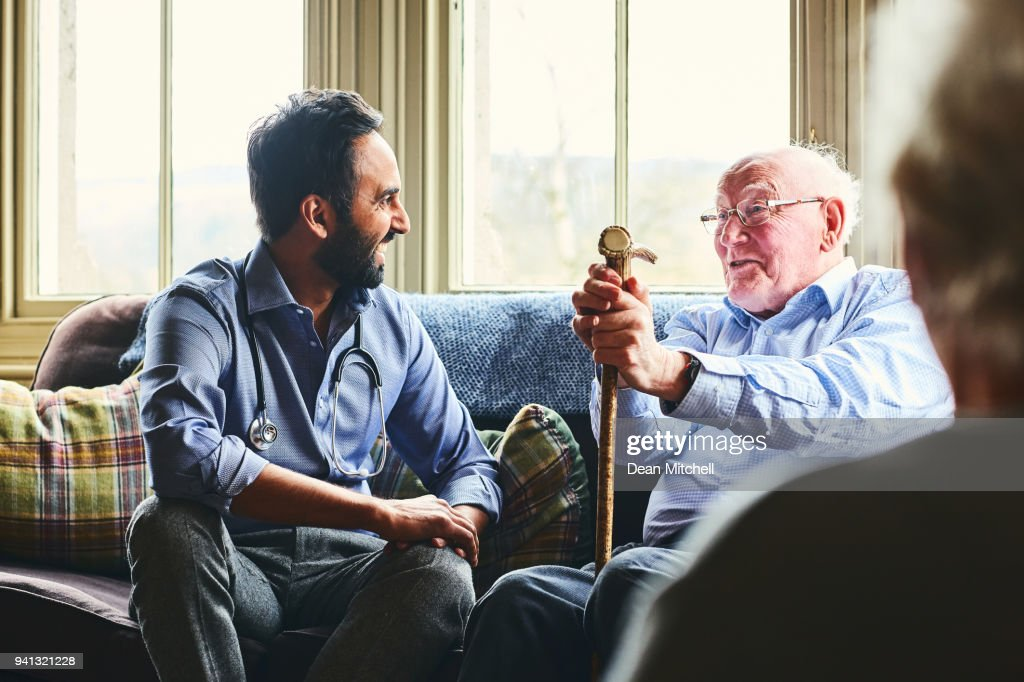 Smiling doctor visiting senior man at home : Stock Photo