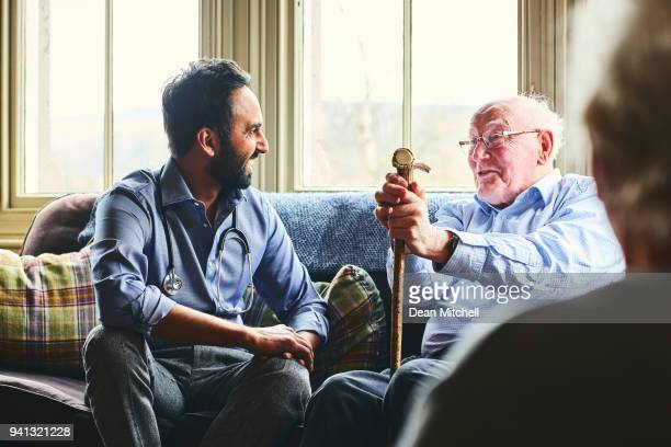 smiling doctor visiting senior man at home - visita imagens e fotografias de stock