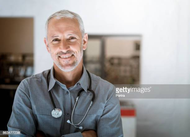 Smiling doctor with stethoscope in hospital