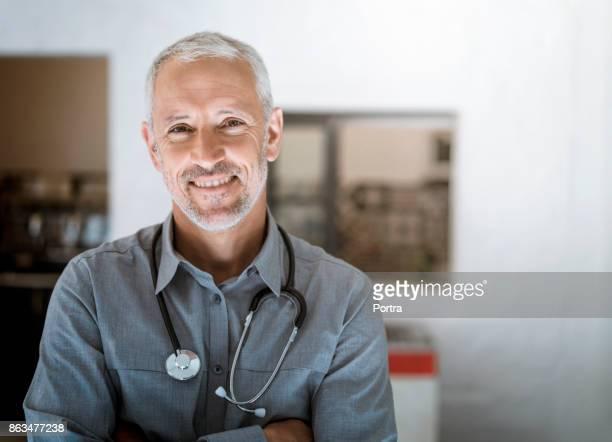 lächelnd arzt mit stethoskop im krankenhaus - hausarzt stock-fotos und bilder
