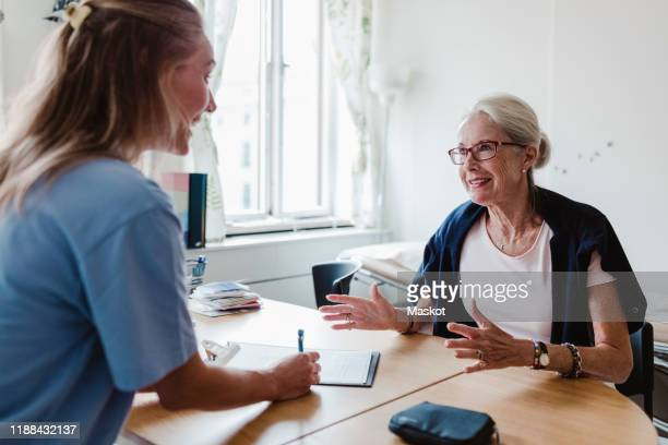 smiling doctor writing prescription while listening to senior woman in hospital - patient stock pictures, royalty-free photos & images