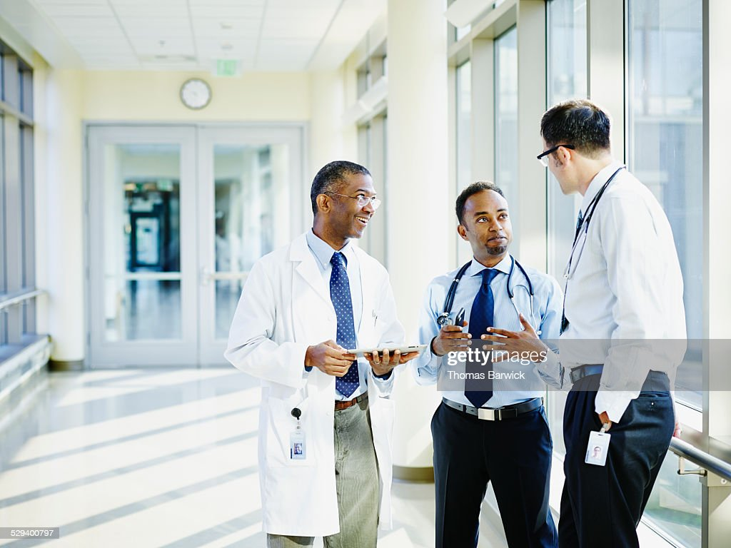 Smiling doctors in discussion in hospital : Stock Photo