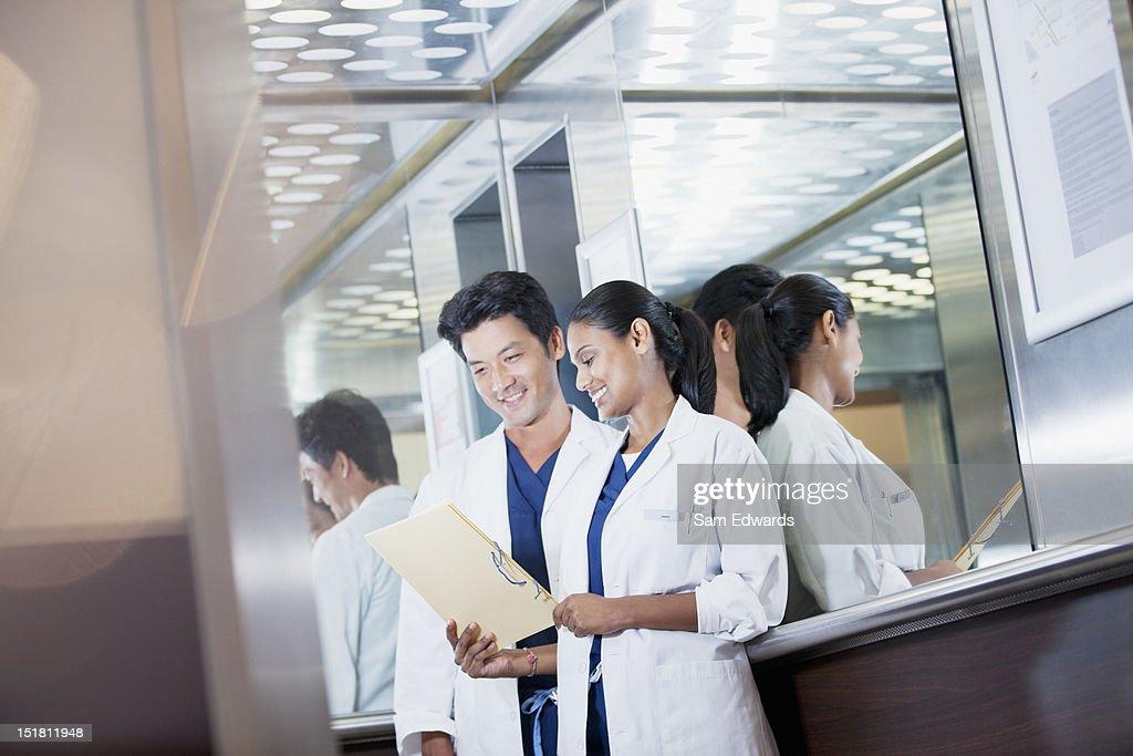 Sonriendo médicos de revisión de registros médicos del hospital ascensor : Foto de stock