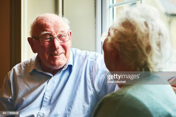 Smiling elderly man talking with a woman