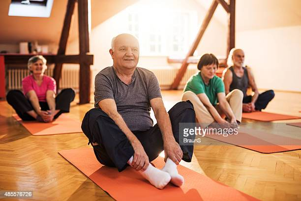 Smiling elderly people doing stretching exercises on a training class.