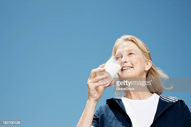 Smiling elderly woman drinking glass of milk