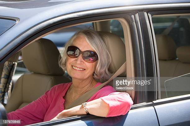 donna anziana sorridente in lato conducente dell'auto - città di west new york new jersey foto e immagini stock