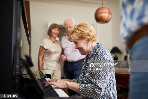 smiling elderly woman playing the piano with friends listening - piano stock pictures, royalty-free photos & images