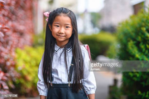 smiling elementary age girl in japanese school uniform - school uniform stock pictures, royalty-free photos & images