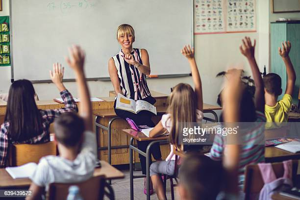 smiling elementary school teacher asking the question in the classroom. - classroom stock photos and pictures
