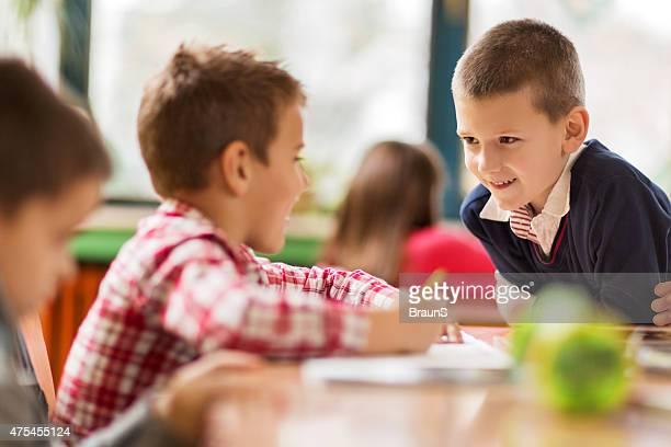 Sonriendo de escuela primaria hablar con su amigo en el aula.