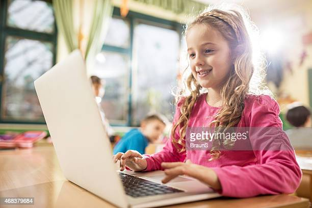 Smiling elementary student using laptop in the classroom.