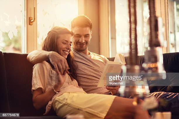 Smiling embraced couple reading a book together at home.