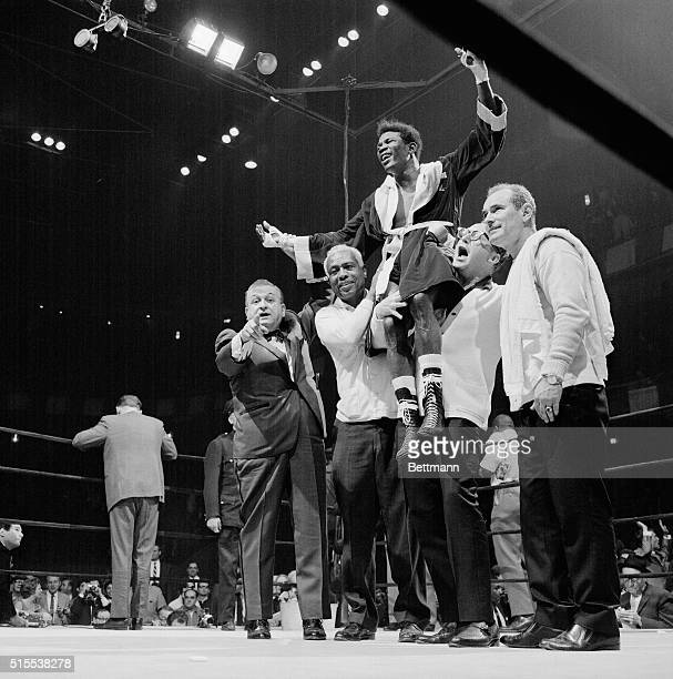 Smiling Emile Griffith gets a victory lift by his handlers after gaining a 15-round decision over middleweight champion Dick Tiger at Madison Square...