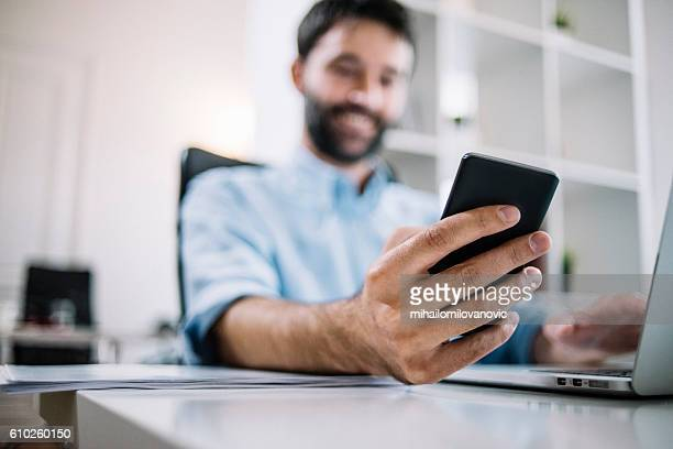 Smiling employee checking email on phone