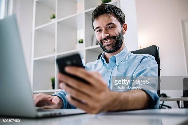 smiling employee checking social media - mihailomilovanovic stock-fotos und bilder