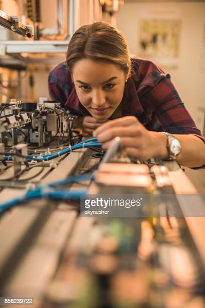 Smiling engineer student examining part of production line in a laboratory.