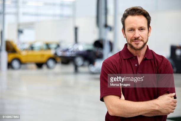 smiling engineer with arms crossed in car industry - vintage auto repair stock pictures, royalty-free photos & images