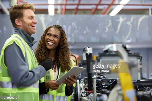 smiling engineers standing with digital tablet - mechanical engineering stock pictures, royalty-free photos & images