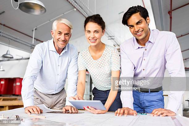Smiling Engineers With Digital Tablet And Blueprint At Desk