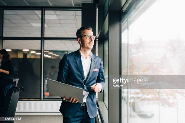 smiling entrepreneur holding laptop while looking through window in office - incidental people stock pictures, royalty-free photos & images