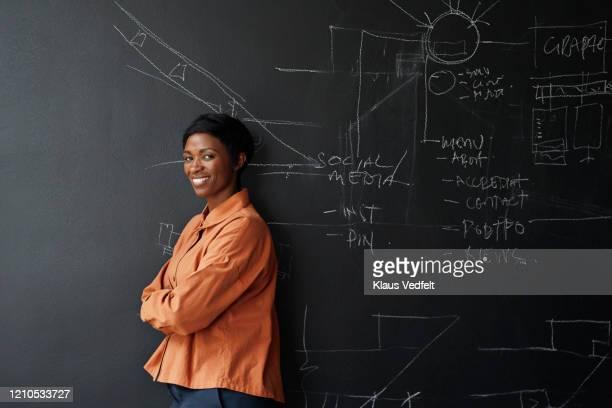 smiling entrepreneur standing in board room - solo una donna giovane foto e immagini stock