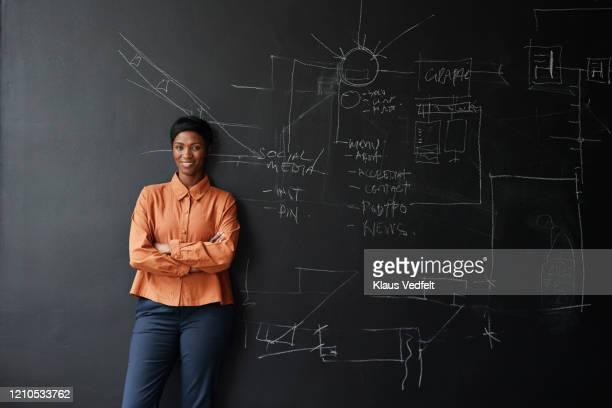 smiling entrepreneur standing in office board room - solo una donna giovane foto e immagini stock
