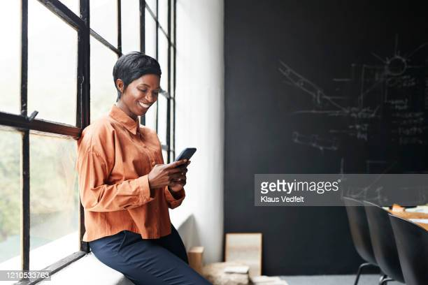 smiling entrepreneur using phone in office meeting - africa stock pictures, royalty-free photos & images