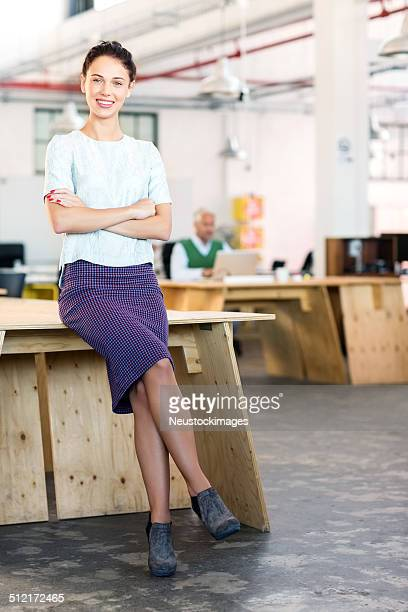 Smiling Entrepreneur With Arms Crossed Leaning On Desk