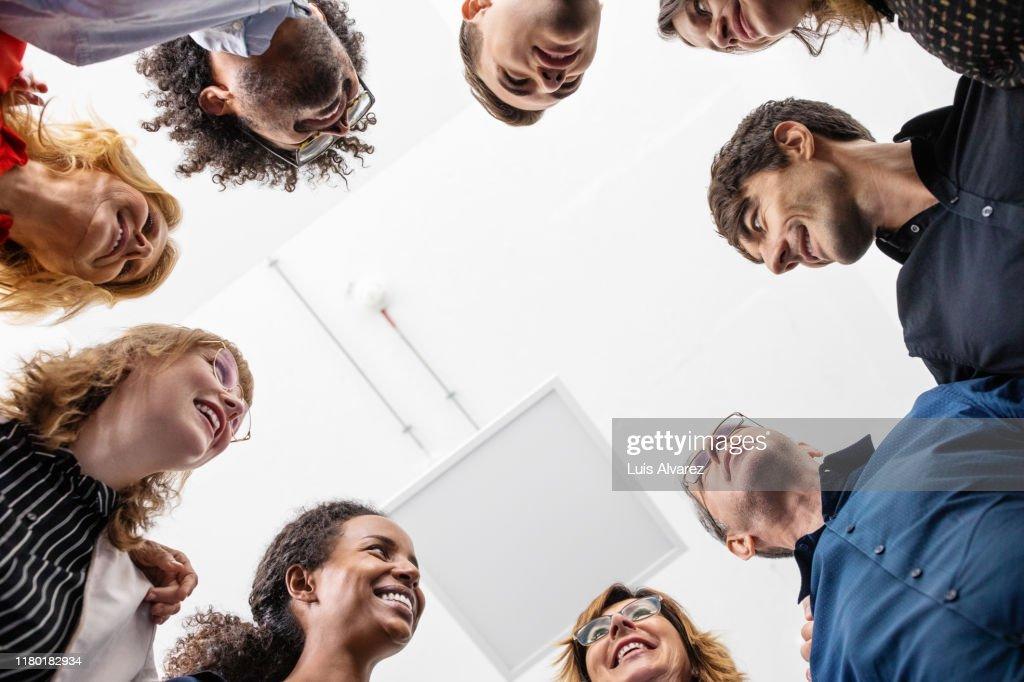 Smiling entrepreneurs huddling together in creative office : Stock-Foto